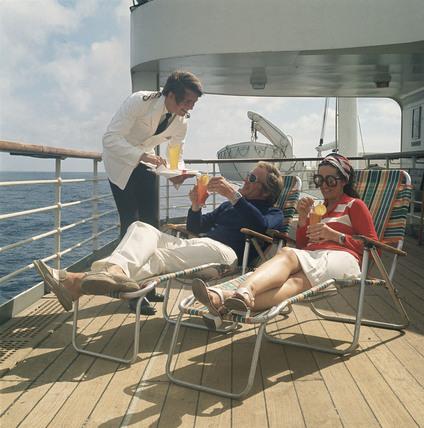A Ships Steward Brings Refreshing Drinks To Passengers Reclining - Steward cruise ship