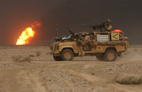 Heavy Machine Gun Platoon, 1st Battalion Royal Irish Regiment travel past a burning oil well, invasion of Iraq, March 2003