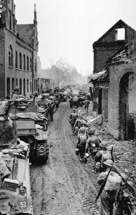 Infantry and tanks moving through Brunen, 1945 (c)