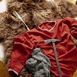 Replicas of finds from the Sutton Hoo Saxon burial site - tunic, chain mail shirt, spear and axe hammer on a bear skin