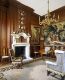 View of the Tapestry room at Antony House showing smoky grey marble chimney-piece, late C17th style settee with oak frame, tapestries of the Greek philosopher Diogenes & chandelier
