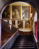 Entrance Hall at Antony House showing the staircase with portraits , oak banisters, and arch