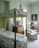 Bedroom with four poster bed at Antony House, showing drapes, dressing table, chest and a portrait