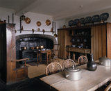 The Kitchen, showing the coal-fired range, with copper and pewter cooking vessels and an early 19th century style settle and a dresser designed by Lutyens in the early 20th century