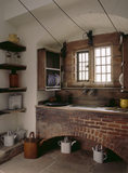 A room view of the scullery including the large sink, wooden draining board and racks, shelves and jars to the left of the window