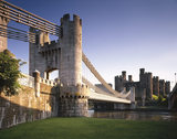 A side view of the Conwy Suspension Bridge looking towards the Castle from below