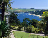 Looking over the garden above the House at Overbecks toward the Salcombe Estuary, where the water is dotted with pleasure craft