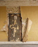 The door in an inmates Sleeping Room, later staff quarters surrounded by peeling wallpaper, revealing many layers underneath