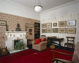 View of the Library at Llanerchaeron showing fireplace and an armchair with a stuffed otter below the side-table