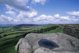 View from Millstone Edge (not NT) on the Longshaw Estate, Derby- shire, with weather worn rocks in the foreground and fields and woodland beyond