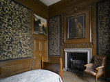 Tobies Chamber with the bed, fireplace, leather armchair, and embroideries on the wall at Hardwick Hall, Derbyshire