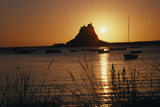 Sunset over sea with Lindisfarne Castle in distance