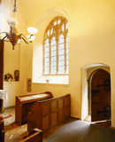 An interior view of the Chapel at Compton Castle, the door ajar, and an impressive arched window is above a wooden pew