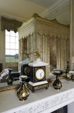 The overmantel mirror and Empire-style black and white marble mantel clock in the Yellow Bedroom at Belton House