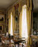 View of the Drawing Room at Calke Abbey, showing the windows, curtains and pier glass