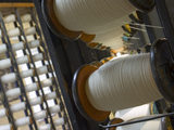 A view of a creel holding the bobbins used for warping which prepares the yarn for the loom at Quarry Bank Mill, Styal