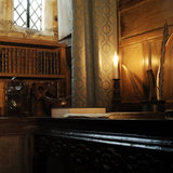 A niche in Meridian at Snowshill Manor, Gloucestershire, with oak panelling, and quill pens and a candle on a table
