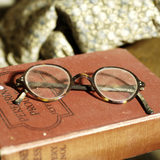 Charles Wade's spectacles resting on a book, part of the collection in the Living Room at the Priest's House, Snowshill Manor