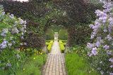 A brick path through the Fuchsia Garden towards the Bathing Pool Garden at Hidcote Manor Garden, Gloucestershire