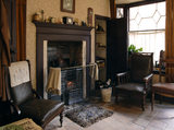 The front parlour of the 1930s house at the Birmingham Back to Backs, with a rug in front of the range and fireplace