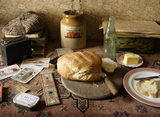 A loaf of bread, some butter, a tin of tobacco and other miscellaneous items on a side table in the parlour of the 1930s house in the Birmingham Back to Backs