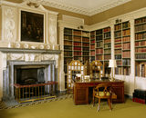 Corner of the Library: fireplace, the Irish desk, bookshelves, three fold velvet screen mounted with signed family and friends photographs