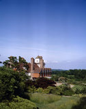 Standen viewed from the south east on a clear blue day, showing parts of the terraced garden