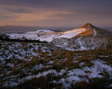 A panoramic view of a snowy Roseberry Common, with the prominent Topping, catching the early morning sun and the horizon lost in the mist