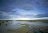 A view of Orford Ness in Suffolk with a stormy sky over mud flats, flanked by greenery