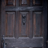 Close shot of the fielded panels of the oak front door and cast-iron door knocker at Hill Top, the home of Beatrix Potter in Sawrey, Cumbria