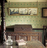 "Close view of section of Beatrix Potter's bedroom at Hill Top Sawrey, showing a section of William Morris' 'Daisy Pattern"" wall paper,a carved oak chest and Bible box and a picture of birds"