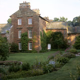 End wing of the house showing parts of the original building, pond and flower beds