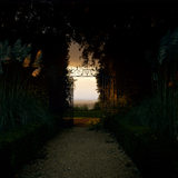"A dramatic picture, looking through an iron gateway, at Hidcote, from a dark leafy ""tunnel"" to the bright sky beyond"