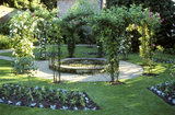 Alexa's Rose Garden at Peckover House with rose-covered arches, a circular central pond and shaped beds with bedding plants