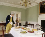 View of the Dining Room at Wordsworth House with a footman laying the table, dressed in the style of the 1770s when William Wordsworth and family lived there