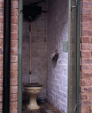 An outside toilet in the communal courtyard of the Birmingham Back to Backs with the water cistern high on the wall, an enamel chamber pot, and newspaper cut & strung for use as toilet paper