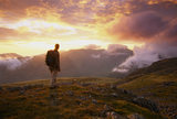 A hiker stands in awe at Wasdale Head as a magnificent sunset colours the sky in reds, pinks and yellows