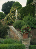 View of a statue and basket weave pot planted with fuchsias on the Orangery Terrace at Powis Castle