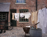 View into Courtyard of 1930's Back to Backs with washing line, dolly tub, washboard, bicycle and pushchair