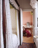 View through Anne Wordsworths Bedroom to the closet beyond with a red silk dress lying on a chair in front of the dressing table at Wordsworth House