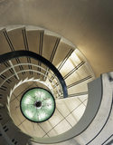 A view looking down the striking spiral staircase at The Homewood designed by Patrick Gwynne is made of concrete with a terrazzo finish and illuminated by a large sunken uplighter at the base