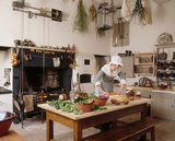 Room view of the kitchen showing the table with vegetables on it, the kitchen range alight and herbs hanging from the ceiling at Wordsworth House