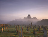 A view of the ruins of Corfe Castle surrounded by mist and in the low grounds are headstones from the nearby cemetery