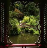 Looking through a window in the China Temple to a pond & bridge, in Biddulph Grange Garden