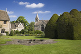A view across the large lawn at the fifteenth-century Great Chalfield Manor, Wiltshire, with the yew house on the right hand side and the Parish Church of All Saints in the centre