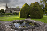 The C14th century Paris Church of All Saints, seen across the lily pond at Great Chalfield Manor, Wiltshire