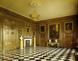 View of the Marble Hall at Belton House, looking towards the fireplace with intricate limewood carving by Edmund Carpenter in the style of Grinling Gibbons