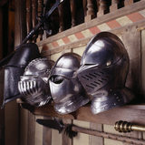 Partial view of four armour helmets hanging on the wall in Dragon at Snowshill Manor