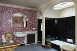 The Bathroom at Hinton Ampner, Hampshire, showing the bath in the black tiled alcove and wash basin and fireplace