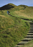 The stepped path leading to the summit of Mam Tor in the Peak District with some people climbing towards the top